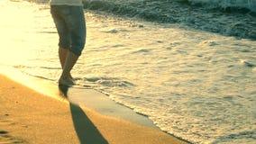 Schattenbildmädchen steht nahe Meer und Wellen rollen sie auf ihren Füßen stock video footage