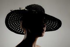 Schattenbildmädchenporträt mit einem Hut Stockfoto