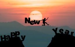 Schattenbildmann springt, um das Wort guten Rutsch ins Neue Jahr zu machen Stockbilder