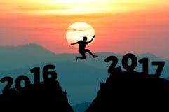 Schattenbildmann springt, um Wort guten Rutsch ins Neue Jahr 2017 mit Sonnenaufgang zu machen (Neues Jahr ist 2017 kommendes Konz stockfotos