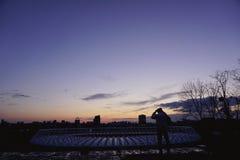Schattenbildmann steht auf Hügel gegen Abend-Sonnenunterganghimmel des Hintergrundes blauen rosa gelben Lizenzfreie Stockbilder