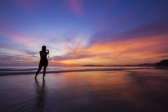 Schattenbildmädchen in erstaunlichem Sonnenuntergang. Stockfotografie