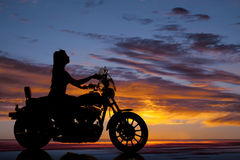 Schattenbildmotorradfrauen-Seitenfahrt lizenzfreie stockfotografie