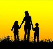 Schattenbildmutter- und -kinderhändchenhalten bei Sonnenuntergang lizenzfreies stockfoto