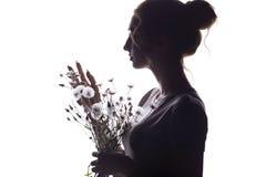 Schattenbildporträt eines Mädchens mit einem Blumenstrauß von trockenen Blumen, Gesichtsprofil einer träumerischen jungen Frau au stockfotografie