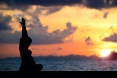 Schattenbildschwangerschaftsyoga auf Strand Stockfoto