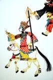 Schattenspiel über einen Mönch, der ein weißes Pferd reitet Lizenzfreie Stockbilder