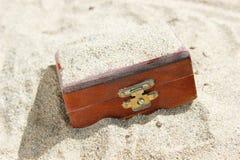 Schatztruhe begraben im Sand stockbild