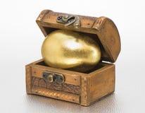 Schatztruhe mit goldenem Ei Stockbilder