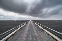 Schauen über der langen Skeidararsandur-Brücke mit einem Sturm auf dem Horizont in Island Lizenzfreie Stockbilder