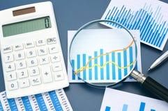 Schauen des Diagramms mit Lupe Berechnung und d analysierend Stockfoto