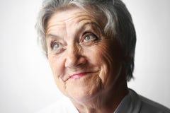 Schauen des Porträts der alten Frau auf einem Grau Lizenzfreie Stockfotografie