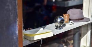 Schauen durch das Kaffeestubefenster, das ein Buch mit einem Hut die Kaffeetasse-Sonnenscheinreflexion liest Stockfotografie