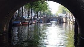 Schauen durch eine Bogenbrücke auf einem niederländischen Kanal mit Booten und Wasser Lizenzfreies Stockbild