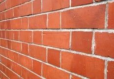 Schauen entlang einer roten Backsteinmauer Stockbild