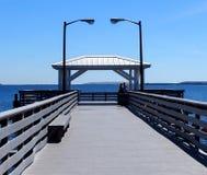 Schauen hinunter einen Pier in den Ozean mit bedecktem verminderndem Perspektive des Dachs blauem Wasser und blauem Himmel Lizenzfreies Stockfoto
