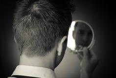 Schauen im Spiegel und Reflektieren Stockbilder