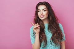 Schauen Sie dort! Überraschte attraktive junge weibliche Dame, die mit dem langen Haar zeigt Gefühle auf Wand trägt Entsetzte Fra Stockbild