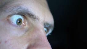 Schauen Sie von der Furcht und Augen eines jungen Mannes auf einem schwarzen Hintergrund ausbauchen stock video