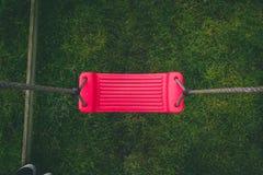 Schauen unten auf einem roten verlassenen Schwingen im Garten lizenzfreie stockbilder