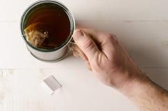 Schauen unten auf Tee- und Mannarm Stockbild