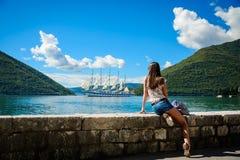Schauendes und Warteerstaunliches weißes Segelboot der schönen jungen Frau Stockfotografie