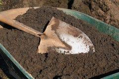 Schaufel im Mutterboden auf grüner Schubkarre Stockfotografie