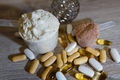 Schaufel mit Molkeprotein und Schaufel mit Schokoladenprotein und Tabletten und Vitamine Omega 3 für Sport und diätetische Nahrun lizenzfreies stockbild