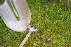 Schaufel und Hacke auf einem grünen Rasen lizenzfreie stockfotos