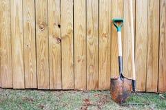 Schaufel und Rührstange auf einem Zaun Stockbild