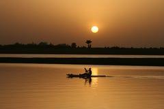 Schaufeln auf dem Wasser am Sonnenuntergang Stockfotos