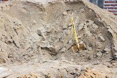Schaufeln Sie festes im Sand an einer Baustelle stockfotos