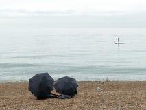 Schaufeln Sie Internatsschüler auf dem Meer mit zwei Regenschirmen im Vordergrund lizenzfreie stockfotografie