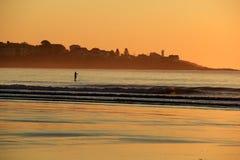Schaufeln Sie Internatsschüler auf Wellen, mit Leuchtturm im Hintergrund Stockfotografie