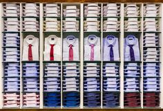Schaukasten mit vielen verschiedenen bunten gefalteten männlichen Modehemden für erwachsene Sammlung auf Lager auf Regalen in der lizenzfreies stockbild