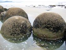 Schaukeln Sie Fluss-Steine im Wasser entlang Küste lizenzfreie stockbilder