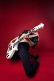 Schaukeln Sie Frau im schwarzen Leder auf roter Spielgitarre Stockbild