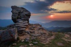 Schaukeln Sie Gebirgsklippe über Sonnenunterganghimmelhintergrund herein Stockfoto