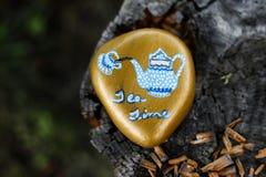 Schaukeln Sie gemaltes Gold mit auslaufendem Tee der blauen und weißen Teekanne in eine Teetasse Stockbild