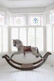 Schaukelpferd im Erkerfenster Stockfotografie