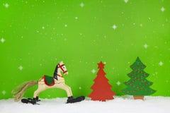 Schaukelpferd und roter Weihnachtsbaum auf grünem Hintergrund Stockfotos