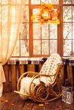 Schaukelstuhl im Raum mit hölzernen Wänden, Weidenkranz im Au Lizenzfreie Stockfotos