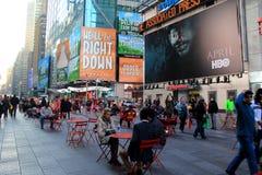 Schaulustige, die durch und gesetzt an den Tischen in der Stadt, Times Square, NYC, 2015 gehen Stockbilder