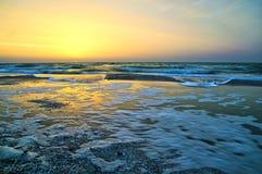 Schaum bewegt auf die Seeküste während des Sonnenaufgangs wellenartig Stockfotografie