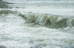 Schaum-Seewelle mit spritzt vom Fliegen auf dem Strand Sturm auf dem Meer Stockbild