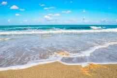 Schaum und Meer bewegen auf eine felsige Seeküste wellenartig Stockfotografie