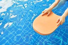 Schaumbrett und Hände mitten in dem Pool, das eine Nische für schwimmende Praxis ist Stockfoto