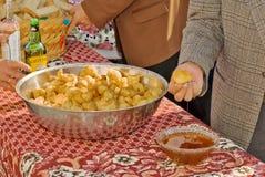 Schaumgummiringe, die in Honig eingetaucht werden, Olympos, Karpathos-Insel, Griechenland Lizenzfreie Stockfotos