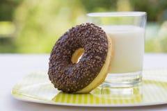 Schaumgummiringe und Glas Milch im Garten Lizenzfreie Stockbilder