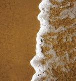 Schaumige Ozeanwelle auf einem sandigen Strand Stockfoto